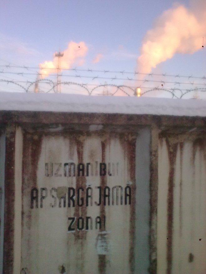 Saulrietā izgaismotie dūmi aiz dzeloņdrātīm
